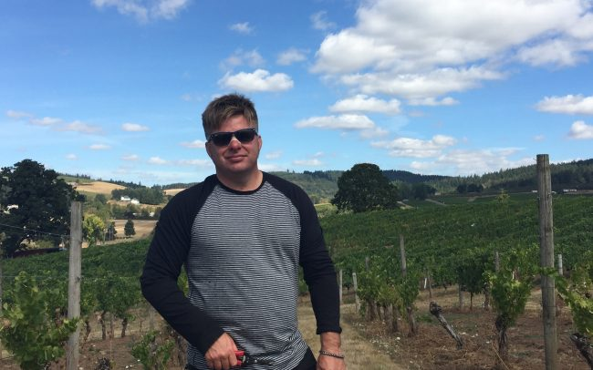 Nick Keeler in the vineyard in sunglasses sampling before harvest